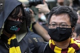 Two young men are dressed in black gowns and wearing yellow and maroon scarves. One man is looking at the other
