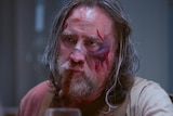Nicolas Cage with long greying hair looks unimpressed. He's wearing a blood-soaked shirt and his face appears beaten.