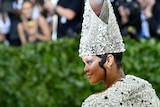 A woman walks past a hedge wearing an intricately decorated dress and matching triangular hat.