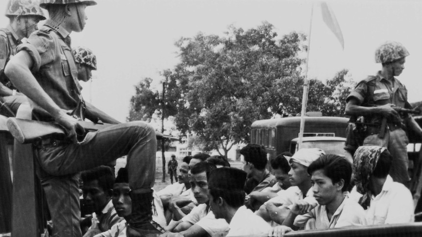 A soldier points a weapons at young men in the back of a truck