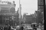 Black and white photo of busy city street corner with neon advertising signs.