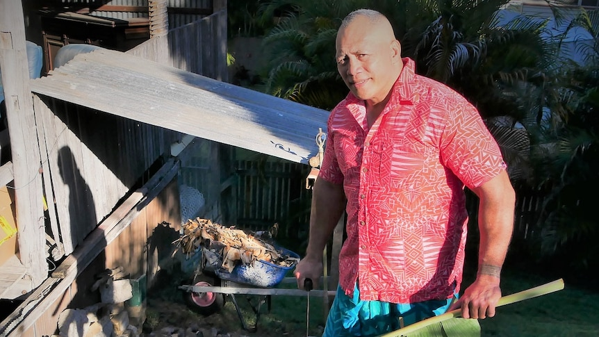 Onehunga Mata'uiau holds a knife and a banana leaf in front of a leant-to.