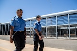 Prison officers walking along fence line