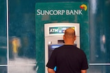 A man withdraws money from a Suncorp ATM