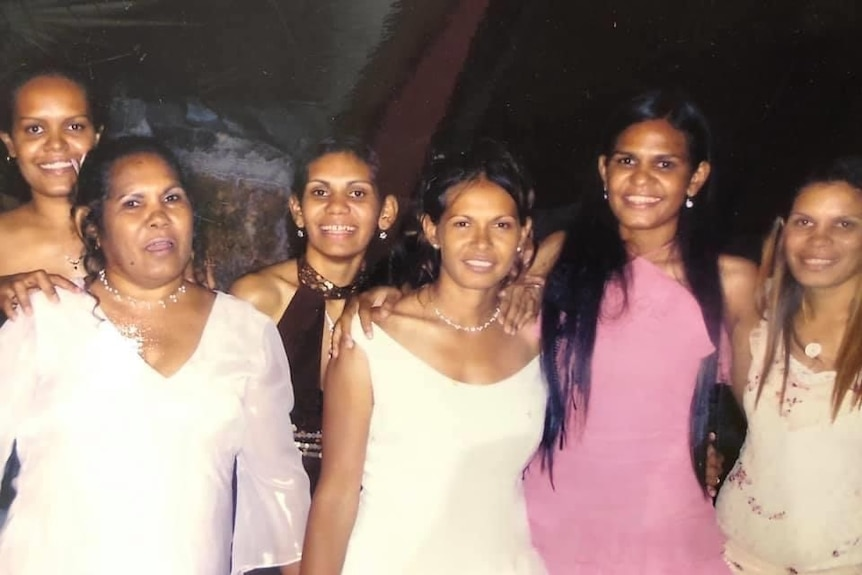 A photo of six sisters in formal dresses.