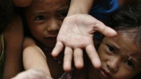Poverty-stricken children reach for food (Reuters: Romeo Ranoco)