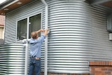 Andy Lemann cleans leaves from the drain outside his renovated house, which is clad in silver corrugated iron.