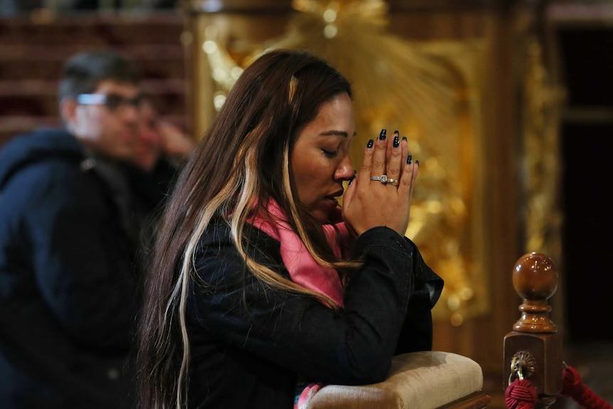 Woman praying in nave of Saint Peter's Basilica, Vatican City.