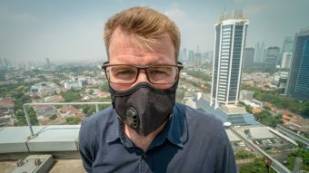 Man stands on a Jakarta rooftop with a face mask.