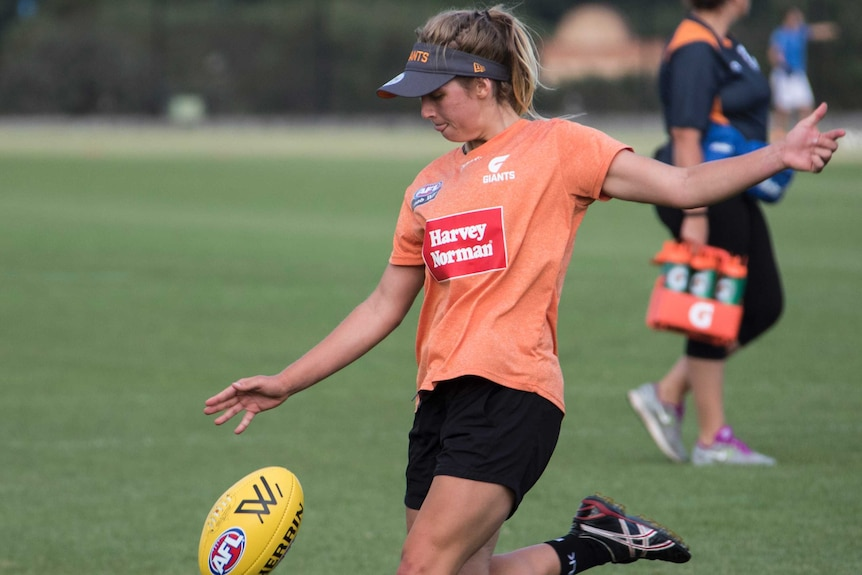 Maddy Collier kicks a football at GWS Giants training.