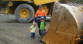 A man and two children stand beside heavy earthmoving machinery