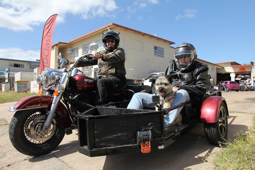 Mechanic Sharine Milne on a motorbike with a man in her sidecar.