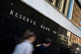 People walk past the Reserve Bank head office in Sydney.