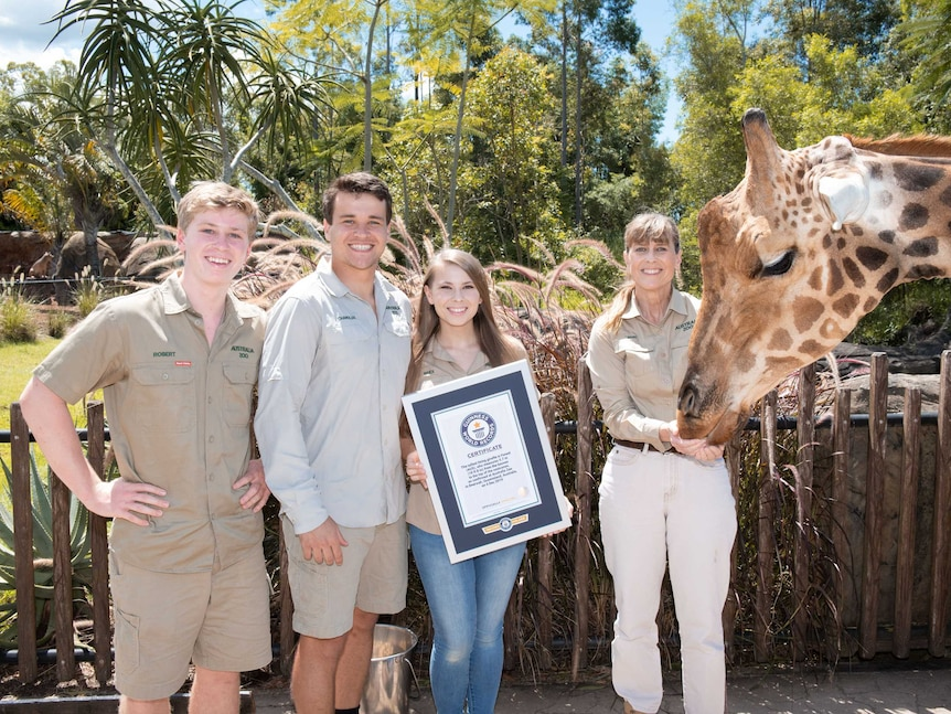 Four people holding an award next to a large giraffe, outdoors.