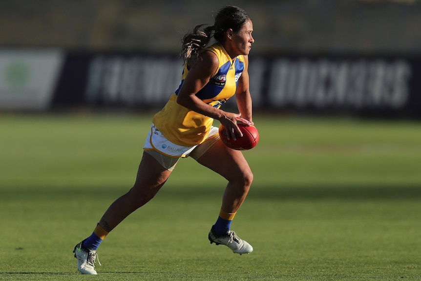 A young indigenous woman playing in the AFLW wearing a yellow guernsey