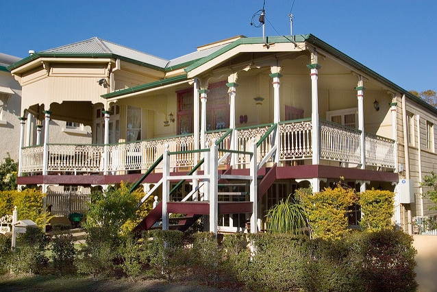 a yellow weatherboard Queenslander against a blue sky shot from street level