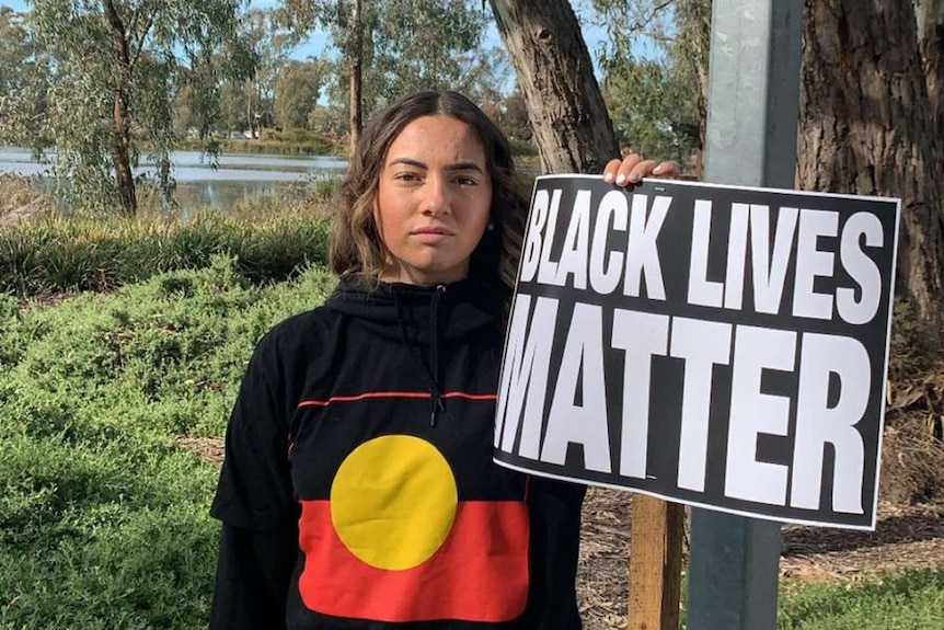"""A young girl stands with a """"Black Lives Matter"""" sign."""