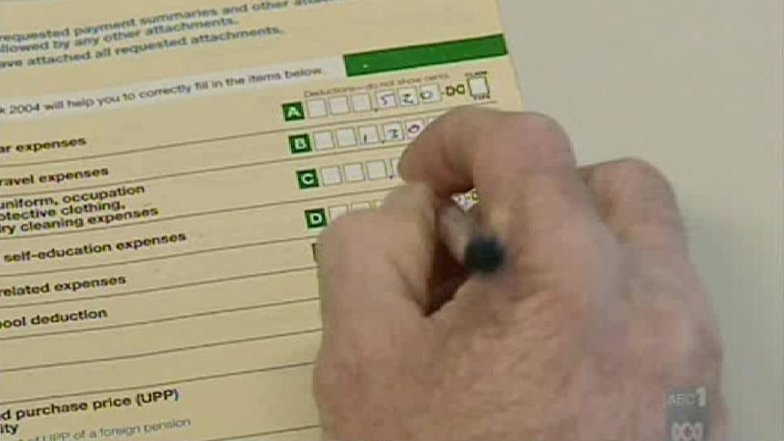Close up of hand writing income information in ATO tax pack