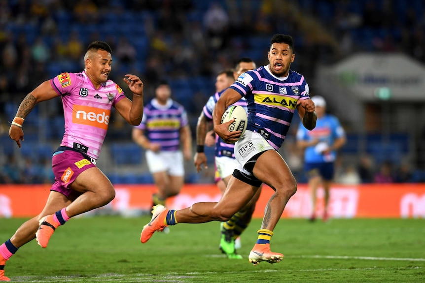 An NRL player runs clear with the ball to score a try as a defender trails behind him.