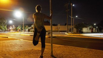 A woman stretches before a night run