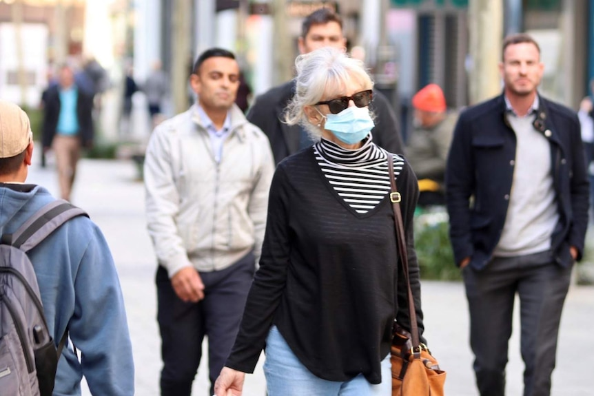 Woman with blue surgical mask walking down outdoor shopping mall, surrounded by several other people not wearing masks.