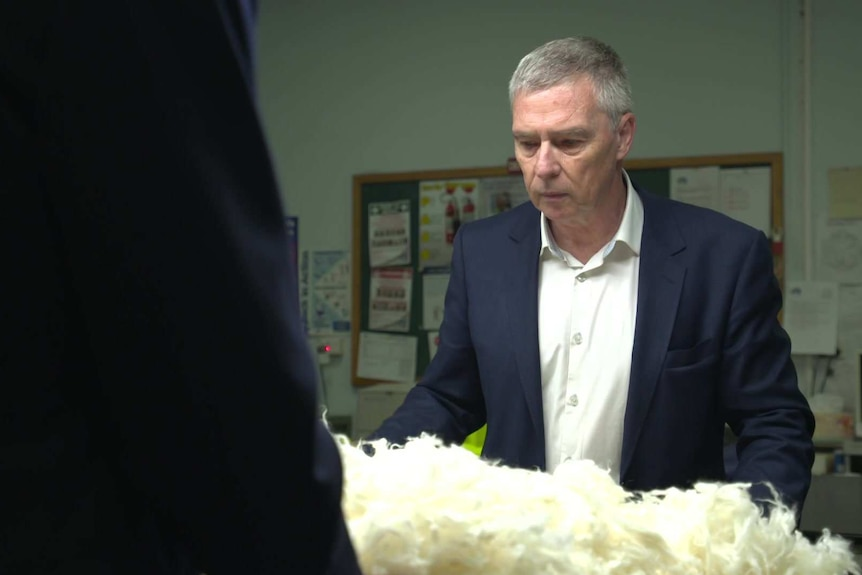 A man in a navy suit stands by a table of fluffy white wool.