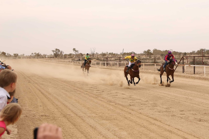 three horses with jockeys on them gallop on a dirt racecourse.  There are spectators.
