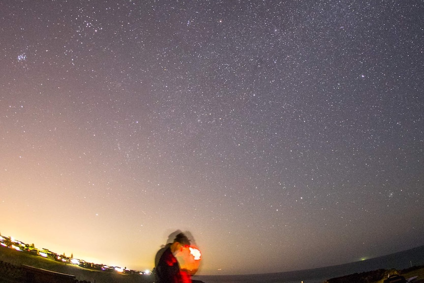 Chris Dengate looks at his phone standing under the night sky filled with stars