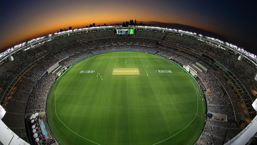 Perth stadium with lights on as the sun sets behind it