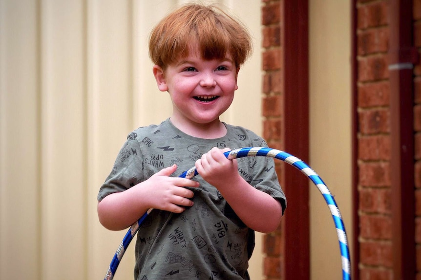A midshot of a small boy with red hair and a green shirt standing in a back yard holding a hula hoop.