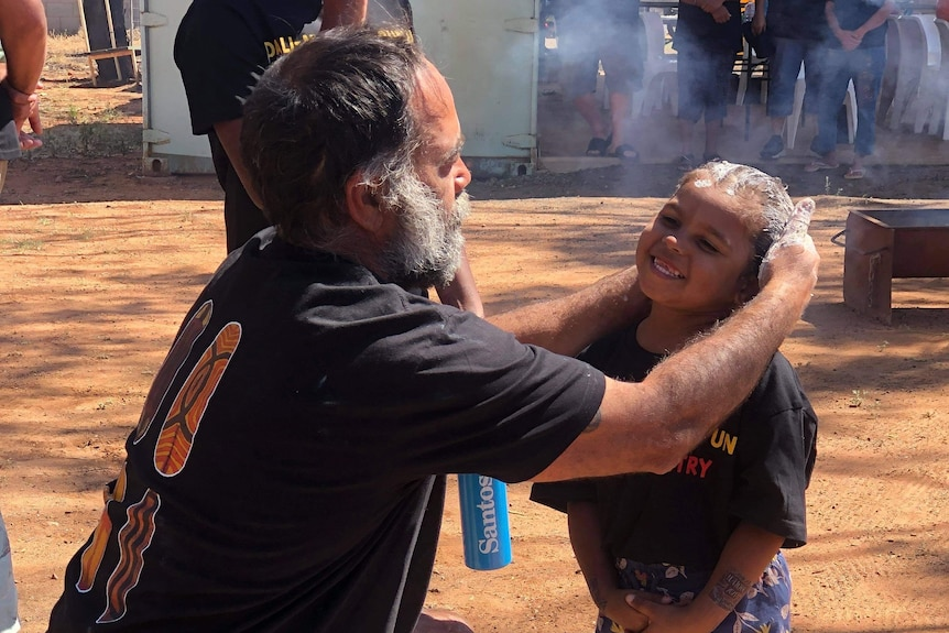 A man paints on a young girls face in preparation for a smoking ceremony.