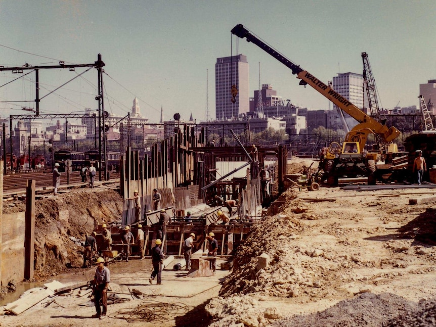Construction works in a rail yard, with Melbourne in the background.