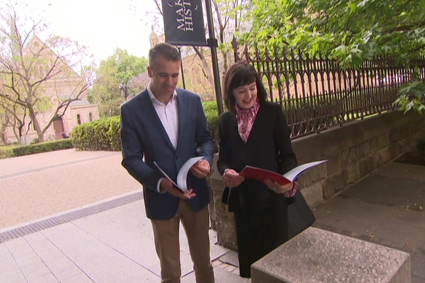 A man and a woman stand next to each other looking over policy booklets in their hands.