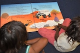Looking over the shoulders of two Aboriginal children sitting next to each other reading a book in language.