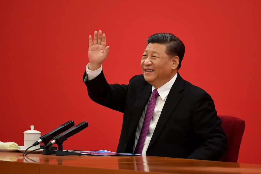 Xi Jinping waves to someone off camera as he sits in a suit in front of a red wall.