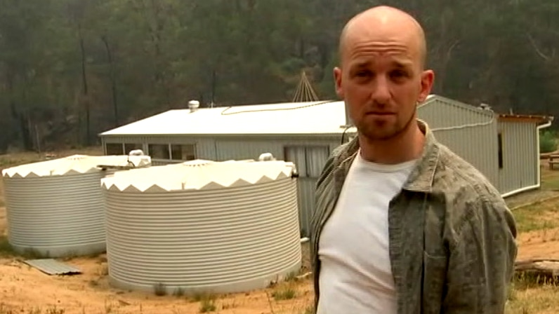 A man stands on a rural property in front of a house and water tanks.