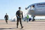 The first 200 US Marines from the 2020 Marine Rotational Force arrive in Darwin wearing face masks.