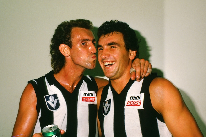 Peter Daicos pretends to kiss Darren Millane on the cheek while holding a beer.