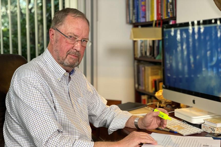 A man sitting a computer desk