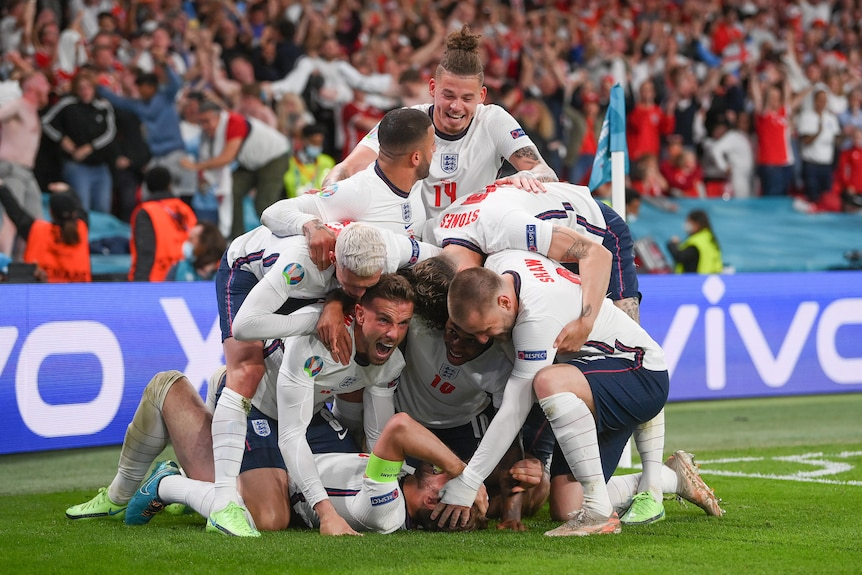 A number of England players pile on top of Harry Kane in celebration