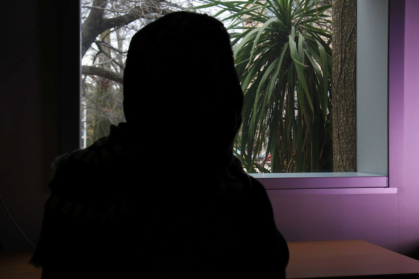 The silhouette of an unidentifiable woman.