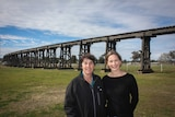 Two woman stand in front of an historic rail viaduct in Manilla NSW