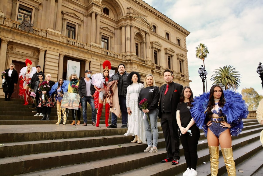 Men and women in colourful costumes stand in front of the steps of an old building.