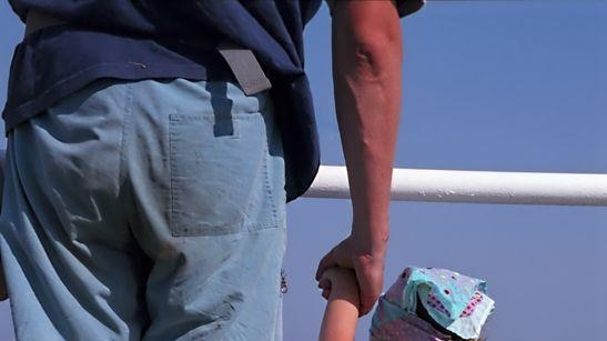 A man, face not visible, holding a toddler's hand. They are facing the sea.