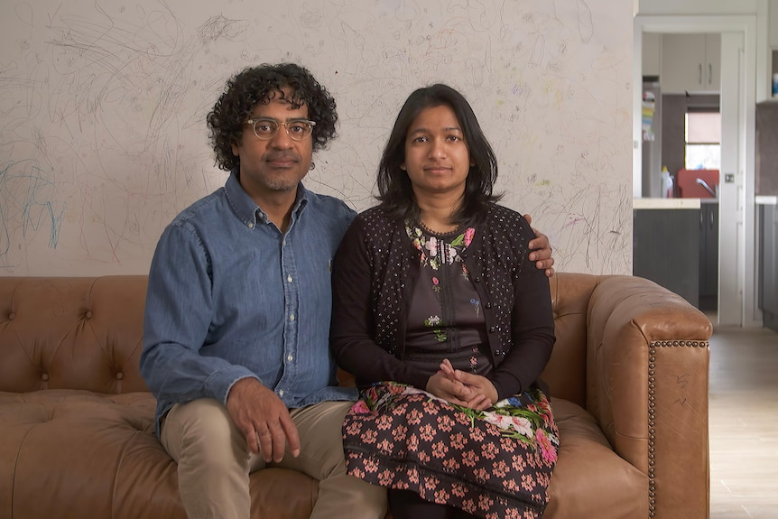 A couple sit on a couch looking directly at the camera with serious expressions