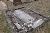 A grave lies flat on the ground in pieces