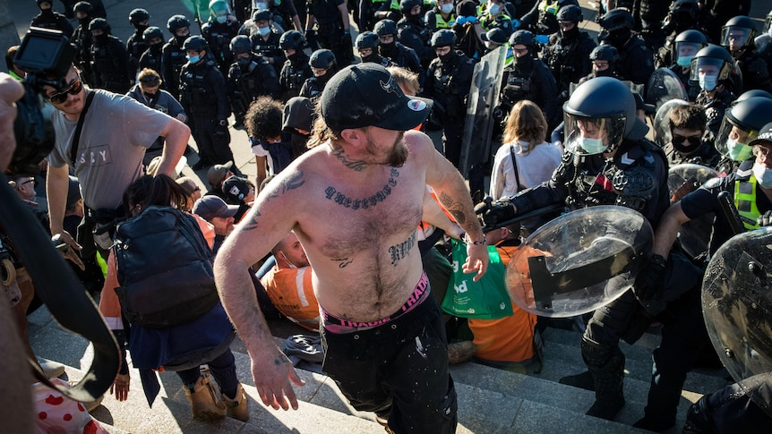 A shirtless tattooed man turns around to face police as they clash with other protestors.