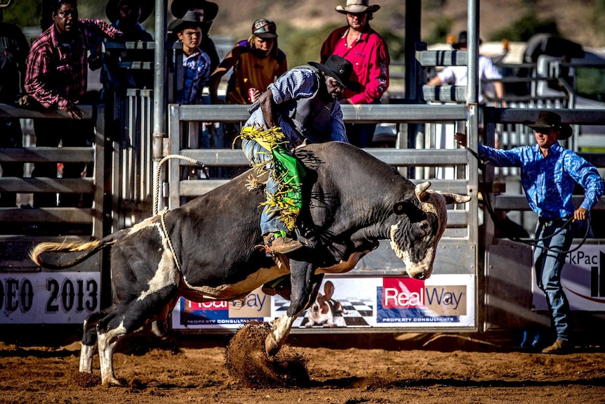 A competitor strains to keep on his bull during the bull riding competition.