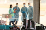 Workers in PPE stand by luggage from a repatriation flight.