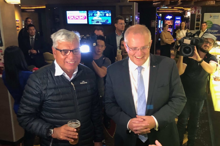 Liberal candidate for Gilmore Warren Mundine holds a beer in a pub while standing next to Prime Minister Scott Morrison.
